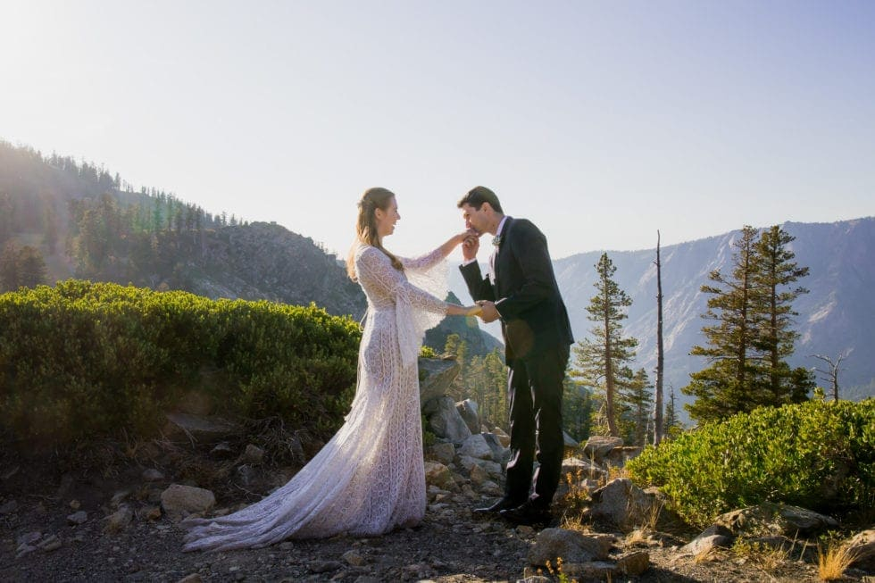 groom kisses brides hand in bear valley