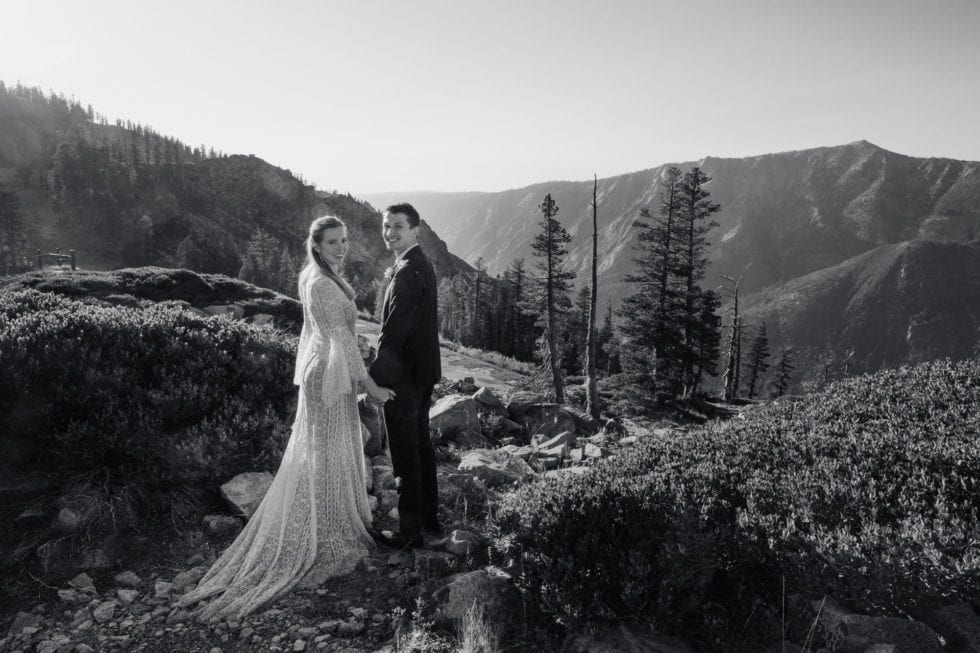 bride and groom standing in front of mountain in bear valley