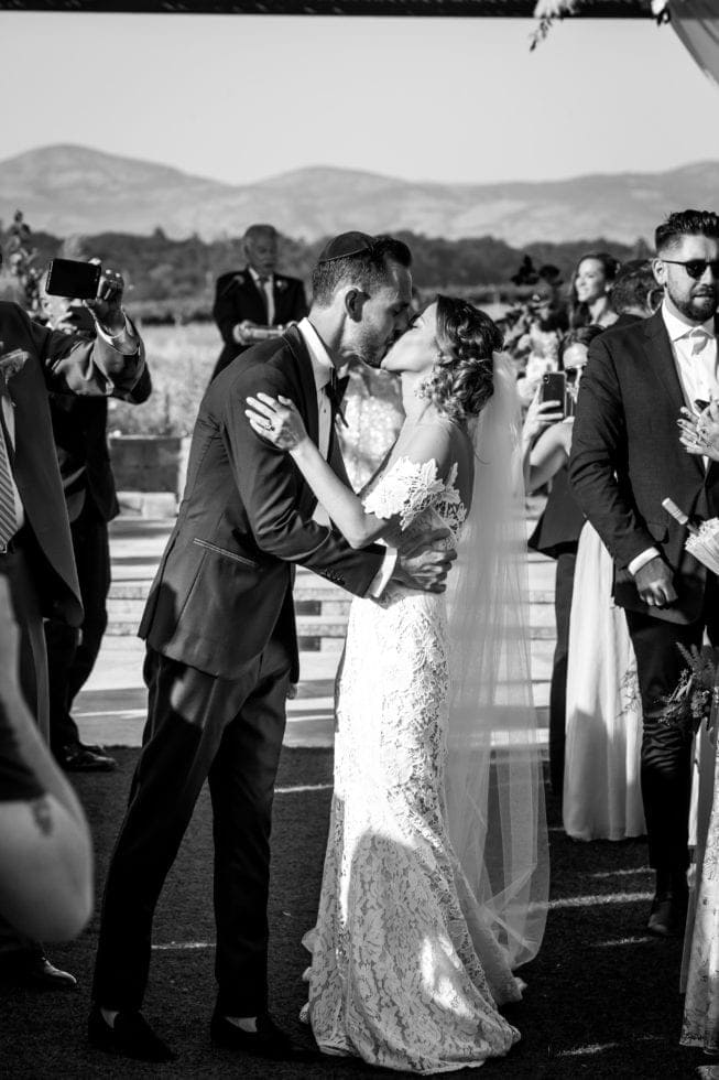 wedding photography of bride and groom kissing in aisle after wedding ceremony